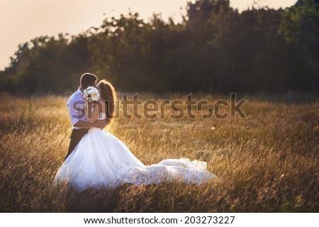wedding. beautiful couple kissing in the sun - stock photo