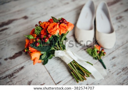wedding bouquet and bridesmaid shoes, boutonniere on a white wooden board. - stock photo