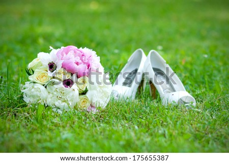 wedding bouquet and shoes lying down on green grass - stock photo