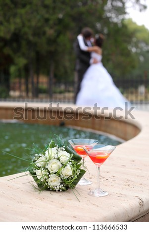 Wedding bouquet and two glasses with red beverage and couple kissing in background - stock photo