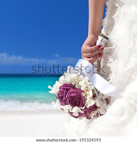 Wedding bouquet in bride's hand on beach  - stock photo
