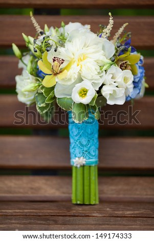 Wedding bouquet of bride. bridal flowers bouquet in wedding day. Wedding bouquet of yellow and white roses and blue fresia and orchids lying on wooden bench - stock photo