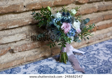 Wedding bouquet of bride. Bridal flowers bouquet in wedding day with blue, white, pink, and green flowers over brick wall - stock photo