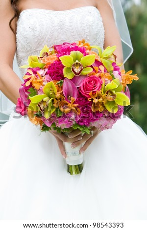 Wedding bouquet of flowers held by a bride. Pink, Orange, and Green - stock photo