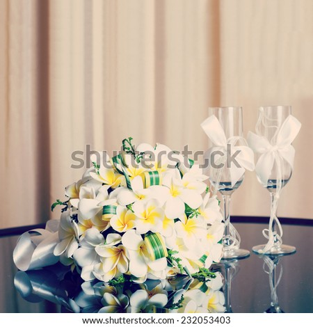 wedding bouquet of frangipani and champagne glasses - stock photo