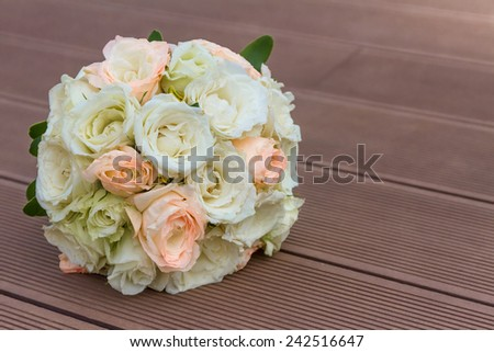 Wedding bouquet of peach and white roses lying on wooden floor - stock photo