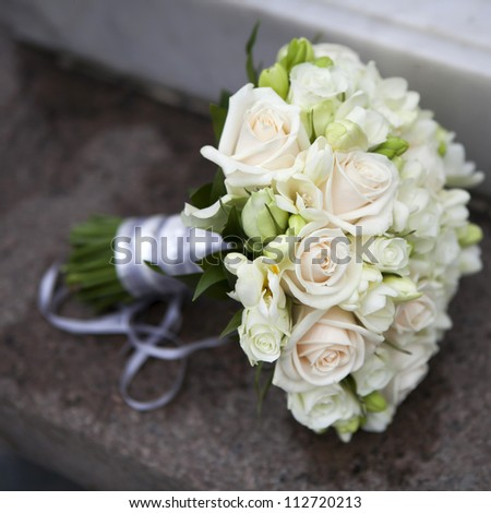 Wedding bouquet of pink and white  roses and blue fresia  lying on bench - stock photo