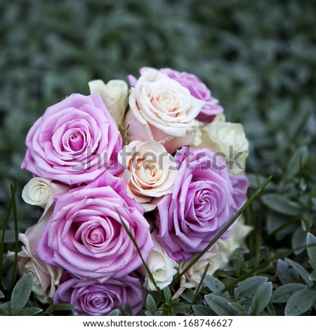 wedding bouquet of pink and white roses lying on grass - stock photo