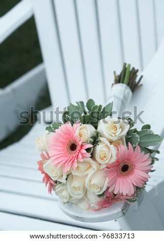 Wedding bouquet of pink daises and white roses on beach chair - stock photo