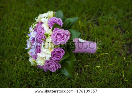 Wedding bouquet of purple and white roses lying on grass - stock photo