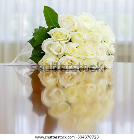 Wedding bouquet of roses for bride at a wedding party. Wedding bouquet of roses on the table against the background of a bright window. - stock photo