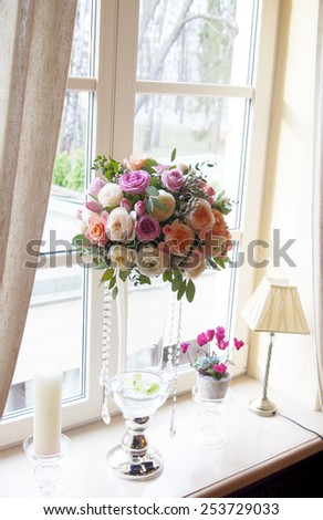 Wedding bouquet of roses in vase on the windowsill - stock photo