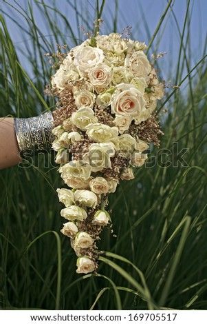 Wedding bouquet of white roses in front of high grass and blue sky , wedding bouquet  - stock photo