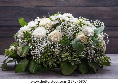 Wedding bouquet of white roses on a wooden table. - stock photo