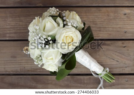 Wedding bouquet of white roses on a wooden table. top view - stock photo