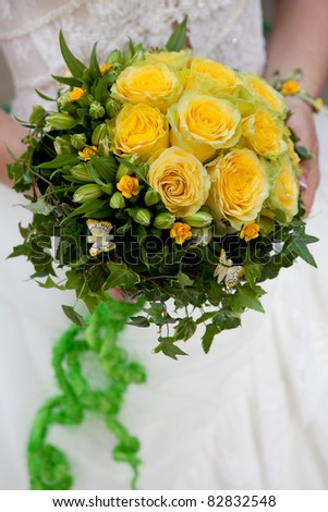 wedding bouquet of yellow roses at girl's hand - stock photo