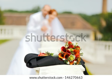 Wedding bouquet with Bride and Groom on background in landscape orientated photo, focused to the Wedding bouquet - stock photo