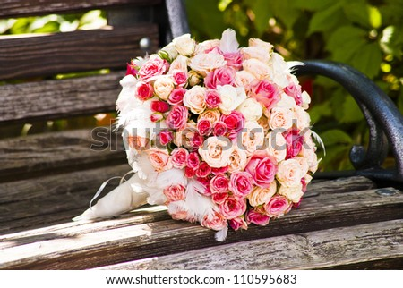 Wedding bouquet with roses on a wooden bench - stock photo