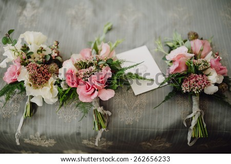 wedding bouquets in a rustic style on vintage bedspread - stock photo