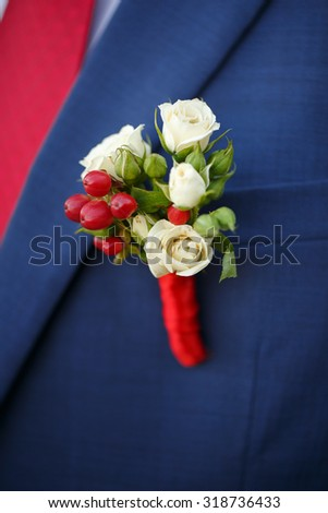 wedding boutonniere from rose on suit of groom - stock photo