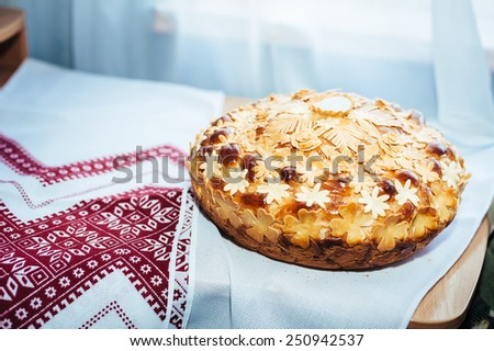 Wedding bread from wheat flour dough decorated with flowers - traditional Ukrainian round loaf an embroidery towel - stock photo