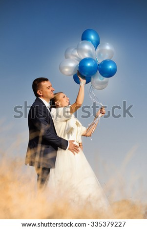 Wedding. Bride and Groom  against blue  sky with balloons - stock photo