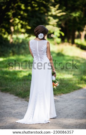 wedding, bride holding a beautiful bouquet behind her back - stock photo