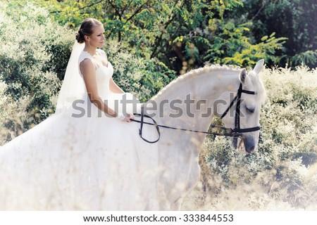 Wedding. Bride on white horse in white flowers - stock photo