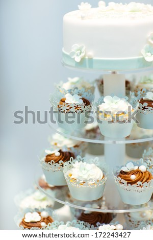 Wedding cake and cupcakes in brown and cream in blue, white and brown - stock photo