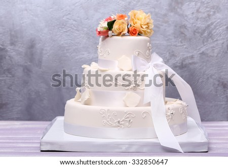 Wedding cake decorated with flowers on grey background - stock photo
