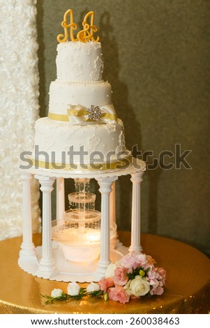 wedding cake for bride and groom with candles and flowers - stock photo