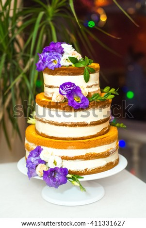 Wedding cake in rustic style on a white plate. Naked cake, decorated with flowers. - stock photo