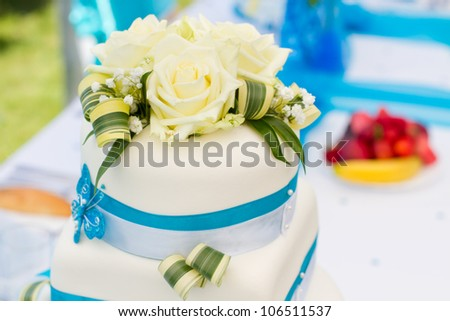 Wedding cake in white and blue combination, adorned with flowers, ribbons and butterflies, focus on flowers - stock photo