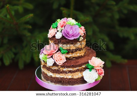 Wedding cake. Naked Wedding cake with flowers - stock photo