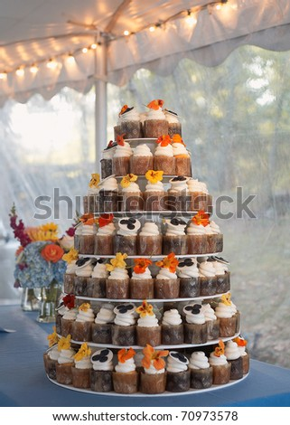 Wedding cake of cupcakes with flowers at reception - stock photo