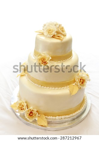 Wedding cake, on white (not isolated) background. 3-tiers covered in ivory fondant sprayed with pearl spray and yellow/gold roses made of sugar paste. - stock photo