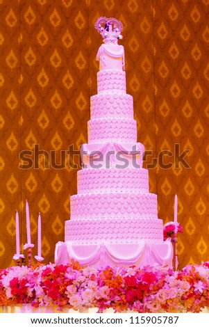 Wedding cake under pink lighting with Thai pattern background - stock photo