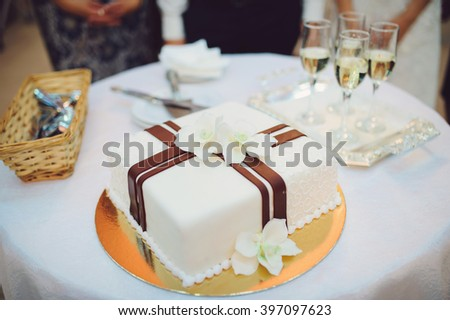 wedding cake with orchids and champagne glasses - stock photo