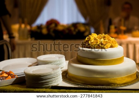 Wedding cake with yellow roses on the table in a restaurant - stock photo