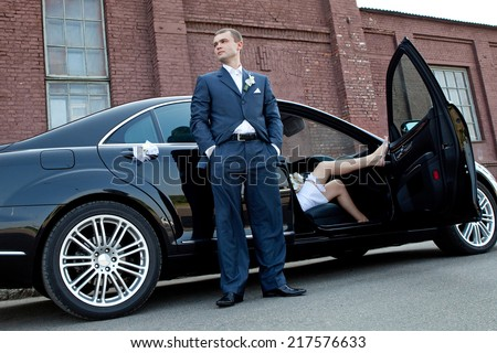 Wedding ceremony. Groom next to an executive car which sits bride. - stock photo
