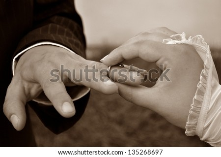 Wedding ceremony moment when the bride just placed the wedding ring on the groom s finger - stock photo