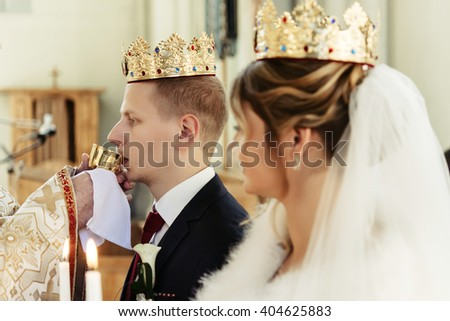 wedding ceremony of happy elegant blonde bride and stylish groom, holding candles in the old church - stock photo