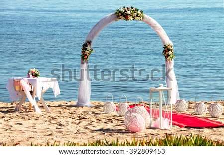Wedding ceremony on a tropical beach in blue. Happy groom and bride under the arch decorated with flowers on the sandy beach. Rose petals fall from above. Wedding and honeymoon concept. - stock photo