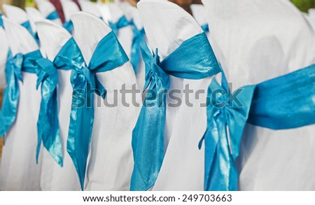 Wedding chairs in row decorated with golden color ribbon - stock photo