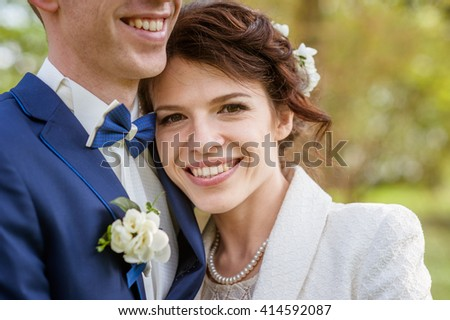 wedding concept. Happy loving newly wed couple looking away while standing in park. Focus on bride - stock photo