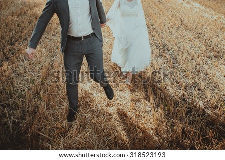 Wedding couple at summer field. Newlyweds spending happy day.  - stock photo