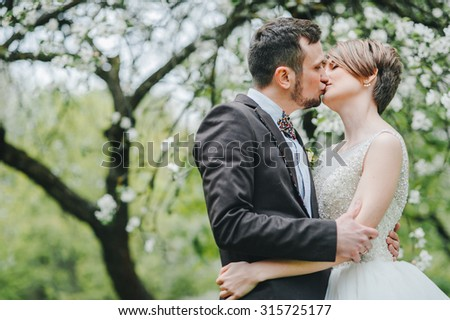 wedding couple. Beautiful bride and groom. Just merried. Close up. Happy bride and groom on their wedding hugging. Groom and Bride in a park. wedding dress. Bridal wedding bouquet of flowers - stock photo