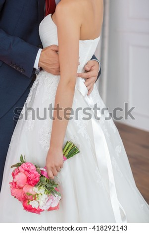 Wedding couple details indoors. Beautiful bride in white dress and pink bridal bouquet of flowers and groom in blue suit close-up. No face, only body and hands. - stock photo