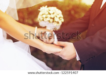 Wedding couple holding hands - stock photo