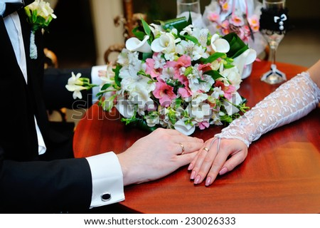 Wedding couple holding hands on bouquet. Groom and Bride in a park. wedding dress. Bridal wedding bouquet of flowers. - stock photo